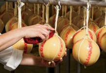 Provolone cheese is hand waxed and stamped at the Belgioioso factory in Green Bay, Wisconsin, Brown County.