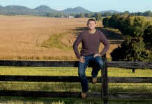 Quint Pottinger sits on a fence overlooking his corn fields which are almost ready for harvest on his farm in New Haven, Kentucky.